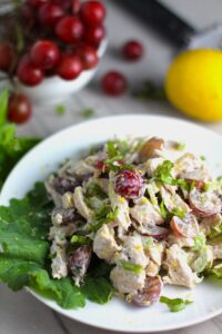 Lemon Basil Chicken Salad with Grapes on a plate on counter with grapes and lemon in background. This recipe is simple, but the taste is anything but simple. It has layers of flavors and textures. You get the hearty texture of the chicken, brightness from the lemon, the fresh and fragrant basil, a slight bite from the onion, and a huge juicy burst of sweetness from the grapes.