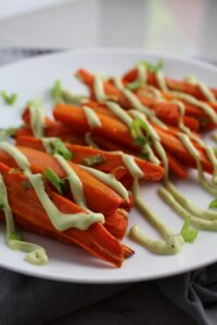 Close up of roasted carrots on plate with avocado crema drizzled on top with scallion slices. Roasted Carrots with smoky cumin and scallions, then topped with Avocado Crema are such a delicious and quick side dish for dinner.  Roasting brings out the natural sugar in the carrots, so they get a sweet caramelization with the salty and smoky flavors. The Avocado crema gives creamy and silky balance.
