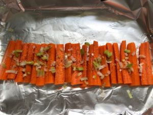 Raw carrots lined up on pan seasoned with sliced scallions over top. Roasted Carrots with smoky cumin and scallions, then topped with Avocado Crema are such a delicious and quick side dish for dinner.  Roasting brings out the natural sugar in the carrots, so they get a sweet caramelization with the salty and smoky flavors. The Avocado crema gives creamy and silky balance.