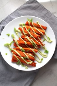 Overhead picture of roasted carrots on plate on gray napkin with avocado crema drizzled on top with scallion slices. Roasted Carrots with smoky cumin and scallions, then topped with Avocado Crema are such a delicious and quick side dish for dinner.  Roasting brings out the natural sugar in the carrots, so they get a sweet caramelization with the salty and smoky flavors. The Avocado crema gives creamy and silky balance.