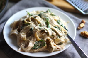Close up of Walnut Sauce recipe with Ricotta and Spinach mixed with Fettuccine on a white plate with fork. The recipe is thick, rich, nutty, and creamy.  It's inspired by the traditional Italian Walnut Sauce from the North-Western Italy, Liguria Region, but my Walnut Sauce recipe adds even more decadence with creamy ricotta and more nutty parmesan cheese.