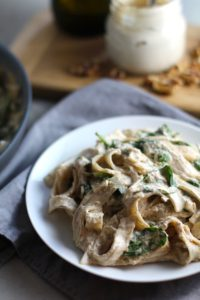 This Walnut Sauce recipe with Ricotta and Spinach on a white plate on napkin with walnuts and jar in background. This recipe is thick, rich, nutty, and creamy.  It's inspired by the traditional Italian Walnut Sauce from the North-Western Italy, Liguria Region, but my Walnut Sauce recipe adds even more decadence with creamy ricotta and more nutty parmesan cheese.