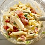 Clear bowl on counter with mixed Mexican Pasta Salad with corn, tomatoes, pasta, Mexican dressing, and cilantro. This Creamy Mexican Pasta Salad has Sun Dried Tomatoes, Corn, Fresh Diced Tomatoes, Cilantro, and smoky Mexican spices. The dressing is creamy and smoky with lots of depth and a hint of sweetness from the Sun Dried Tomatoes that are blended in. Terrific as a side or mix in some chicken or beef and call it a meal!