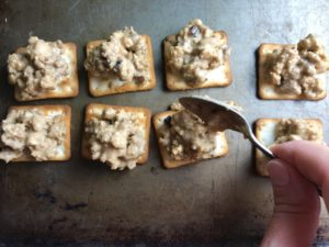 Adding Hanky Panky Meat topping to GF crackers on sheet pan. These Hanky Panky Canapes are the BEST Party Appetizers around! They cheesy, meaty, and absolutely delicious. Ground Beef is mixed with Homemade Chicken Sausage and then combined with lots of cheese until its a creamy addictive pot of goodness. Then it is scooped on top of bread, toasts, or crackers