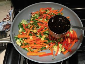 Adding Soy Sauce to stir fry veggies in pan for Asian Lettuce Wraps. They are a fantastic way to use leftover Turkey or Chicken transforming it with new delicious flavors and textures. The turkey is stir fried with carrots, red pepper, and brussel sprouts in a flavorful ginger, garlic, & sesame sauce. It's layered in lettuce wraps with rice and a cool, crunchy purple cabbage sesame slaw. Serve with a Garlic Honey Soy Sauce....YUM!!!