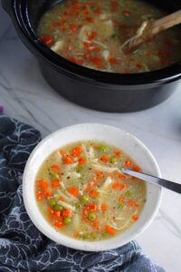 5-Ingredient Homemade Chicken Soup in a bowl with spoon and crockpot in background. This soup is thick, creamy, and hearty. It's filled with flavorful broth, meaty shredded chicken, and sweet bursts of bright veggies. You can prepare all of the ingredients ahead and freeze them until you are ready to cook. Then, thaw, pour into the Slow Cooker, set and forget.