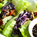 Asian Lettuce Wraps on a plate with sauce. They are a fantastic way to use leftover Turkey or Chicken transforming it with new delicious flavors and textures. The turkey is stir fried with carrots, red pepper, and brussel sprouts in a flavorful ginger, garlic, & sesame sauce. It's layered in lettuce wraps with rice and a cool, crunchy purple cabbage sesame slaw. Serve with a Garlic Honey Soy Sauce....YUM!!!
