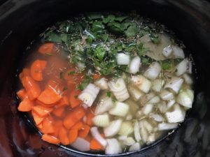 Carrots, onion, broth and other ingredients in crockpot for the Slow Cooker Beef Stew over Noodles recipe.  It's comfort food full of flavor and texture with carrots, onion, garlic, thyme, beef, and more. Now, try pouring that salty, chunky, saucy goodness over noodles...yup, even more amazing!  #beefstew #crockpot #slowcooker #easydinners #dinnerrecipes