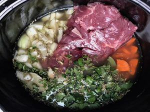 Beef, carrots, onion, broth, and other ingredients in crockpot for the Slow Cooker Beef Stew over Noodles recipe.  It's comfort food full of flavor and texture with carrots, onion, garlic, thyme, beef, and more. Now, try pouring that salty, chunky, saucy goodness over noodles...yup, even more amazing!  #beefstew #crockpot #slowcooker #easydinners #dinnerrecipes