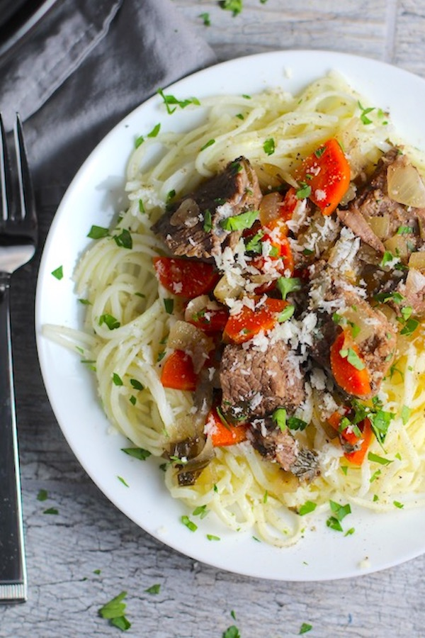 Slow Cooker Beef Stew over Noodles on a plate.  This is downhome comfort food that's full of flavor and texture with carrots, onion, garlic, thyme, beef, and more. Now, try pouring that salty, chunky, saucy goodness over noodles...yup, even more amazing!