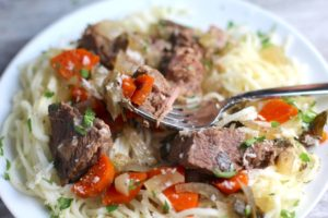 Slow Cooker Beef Stew over Noodles on a plate with fork. This is downhome comfort food that's full of flavor and texture with carrots, onion, garlic, thyme, beef, and more. Now, try pouring that salty, chunky, saucy goodness over noodles...yup, even more amazing!#beefstew #crockpot #slowcooker #easydinners #dinnerrecipes