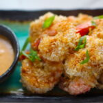 Baked Coconut Shrimp on plate with Sriracha Sauce. Crunchy and utterly irresistible, this 30-Minute Baked Coconut Shrimp recipe is one that you have got to try!  They are baked, not fried, so they are EASY to cook and HEALTHIER for you too!