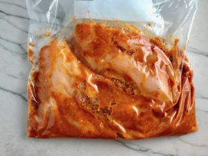 Sun Dried Tomato sauce in bag with raw chicken. Sun Dried Tomato Chicken is slightly sweet, slightly tart and tangy, and hugely delicious! When Sun dried tomatoes are rehydrated and blended, they turn into a thick and lucious sauce that coats the chicken keeping it moist and juicy when it simply bakes in the oven. It's a perfect easy weeknight dinner that you can prepare ahead and cook quickly! #chicken #chickenrecipes #easydinners #dinnerrecipes