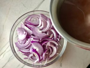 Red Onions in bowl before pickling for Slow Cooker Pork Tacos with with Pickled Onions, Shredded Cheese, and Cilantro Lime Crema drizzled on top! It's such an easy dinner since the pork cooks in the slow cooker to be perfectly seasoned and fall apart tender. #tacos #easydinner #glutenfree #dinner #mexican #pork
