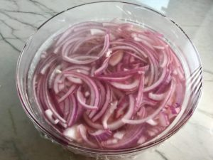 Red Onions pickling in vinegar in bowl for Slow Cooker Pork Tacos with with Pickled Onions, Shredded Cheese, and Cilantro Lime Crema drizzled on top! It's such an easy dinner since the pork cooks in the slow cooker to be perfectly seasoned and fall apart tender. #tacos #easydinner #glutenfree #dinner #mexican #pork