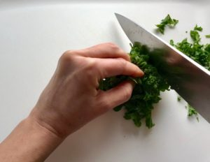 Chopping Kale for Quinoa & Kale Salad with Roasted Chickpeas, Pomegranate, Feta, red pepper, and Creamy Lemon Dressing.#glutenfree #lunch #dinner #healthyrecipes #healthyfood #salads #quinoa #kale