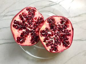 Pomegranate cut in half on plate for Quinoa & Kale Salad with Roasted Chickpeas, Pomegranate, Feta, red pepper, and Creamy Lemon Dressing.#glutenfree #lunch #dinner #healthyrecipes #healthyfood #salads #quinoa #kale