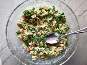 Quinoa & Kale Salad in clear glass bowl with spoon with Roasted Chickpeas, Pomegranate, Feta, red pepper, and Creamy Lemon Dressing.#glutenfree #lunch #dinner #healthyrecipes #healthyfood #salads #quinoa #kale