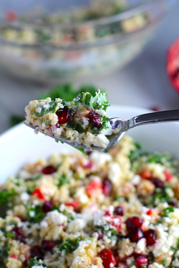 Fork with bite of Quinoa & Kale Salad with Roasted Chickpeas, Pomegranate,Feta, and Creamy Lemon Dressing.#glutenfree #lunch #dinner #healthyrecipes #healthyfood #salads #quinoa #kale