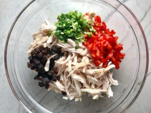 Shredded chicken, red pepper, scallion, and raisins in bowl for Curry Chicken Salad. It has so many fantastic flavors and textures!  The chicken breast is simply roasted and mixed with a creamy sweet and savory curry dressing.  Red pepper gives you a fresh crunch, scallion gives a savory bite, and raisins give a burst of sweet.  #chicken #chickenrecipes #chickensalad #currychicken #mealprep #lunch #healthyrecipes