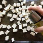 Hand spraying tofu pieces with olive oil for Roasted Tofu Croutons. These are seasoned and toasted for the perfect addition to any salad, pasta, rice, or soup!   They get a roasted, almost nutty flavor with a salty and smoky seasoned crust with a chewy bite.  Super easy to make, low carb and great source of protein!  #croutons #salad #tofu #tofurecipes #vegetarian #plantbased #paleo