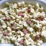 Raw Cauliflower Cordon Bleu Bake in dish. It layers in nutty and salty Gruyere Cheese, with a creamy Vegetable broth based sauce with garlic and parsley. Then the ham and cauliflower are folded into all of this goodness and it's baked in the oven until it all becomes one knock-your-socks-off dish! #cauliflower #lowcarb #glutenfree #casserole #onepot #familydinner #mealprep #easydinner #dinner #healthydinner #healthyfood #healthyrecipes