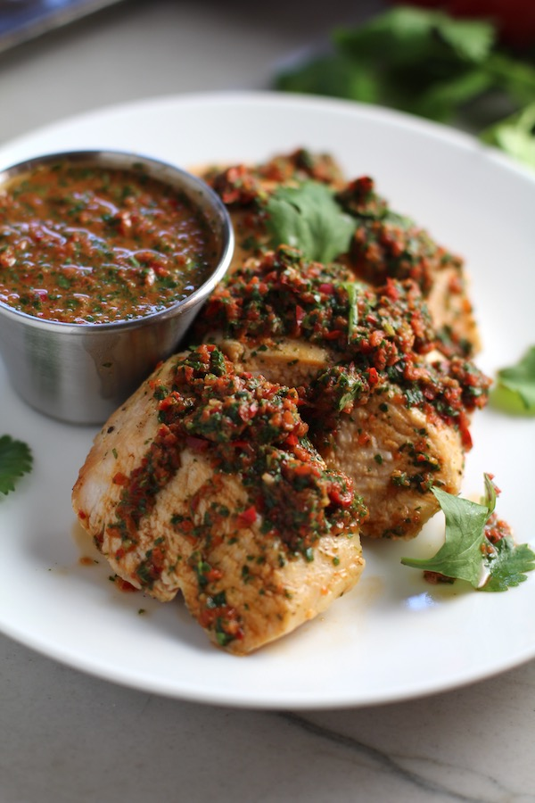 Chicken Chimichurri Rojo on a plate with fresh cilantro and a cup of chimichurri. It is roasted Chicken topped with a cool, fresh, tangy, and incredibly full-flavored! The Rojo comes from the addition of red pepper. All of the ingredients simply get blended in a food processor so it could not be easier! #chicken #chickenrecipes #chimichurri #easychicken #easydinners #dinner