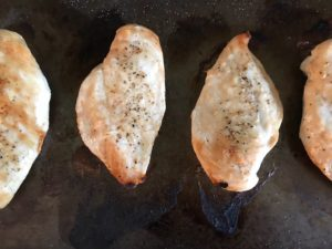 Broiled Chicken on pan for the Chicken Chimichurri Rojo. It is broiled or grilled Chicken topped with a cool, fresh, tangy, and incredibly full-flavored! The Rojo comes from the addition of red pepper. All of the ingredients simply get blended in a food processor so it could not be easier! #chicken #chickenrecipes #chimichurri #easychicken #easydinners #dinner
