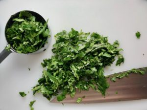 Chopped cilantro on cutting board for Cilantro Lime Quinoa. It's fluffy, nutty, citrusy, salty, and the perfect accompaniment for any protein or vegetable! With just a few simple ingredients, you can make this fantastic healthier alternative to rice. #quinoa #quinoarecipes #sides #healthyfood