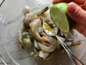 Squeeze lime over raw shrimp for Garlic and Lime Shrimp with Tzatziki Sauce.  The Shrimp is simply sauteed with minced garlic, olive oil, and lemon for big bold flavors. The Tzatziki Sauce is bright and cool with creamy yogurt with fresh cucumber, lime, garlic, and scallion. #shrimp #easydinner #dinner #seafoodrecipes #shrimprecipes