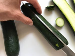 Cutting zucchini in half for Spinach Artichoke Stuffed Zucchini. Each fantastic bite gives you creamy artichoke, nutty cheesy Parmesan, spinach, and zucchini. Prepare entirely ahead, then bake 20 minutes and enjoy! #vegetarian #zucchini #stuffedzuchini #spinach #artichoke #springrecipes #healthyfood #healthydinner #healthyrecipes #glutenfree