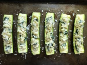 Stuffed raw zucchini halves for Spinach Artichoke Stuffed Zucchini. Each fantastic bite gives you creamy artichoke, nutty cheesy Parmesan, spinach, and zucchini. Prepare entirely ahead, then bake 20 minutes and enjoy! #vegetarian #zucchini #stuffedzuchini #spinach #artichoke #springrecipes #healthyfood #healthydinner #healthyrecipes #glutenfree