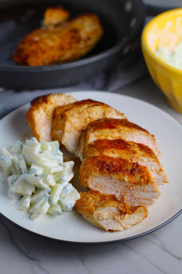 Hungarian Paprika Chicken sliced on plate with Cucumber Salad on the side. The paprika gives beautiful color and a deep, peppery flavor. #chicken #easychicken #easydinner #dinner #healthydinner