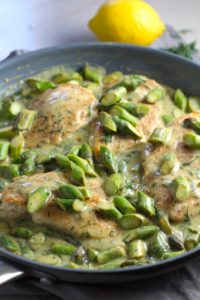 Cooked Lemon Dill Sauce Chicken and Asparagus in pan on stove. It has chicken in a light and creamy sauce flavored with garlic, lemon and fresh dill. It's loaded with fresh asparagus. #springrecipes #dinner #easydinner #healthydinner #lemon #asparagus #chicken #glutenfree #easyrecipes