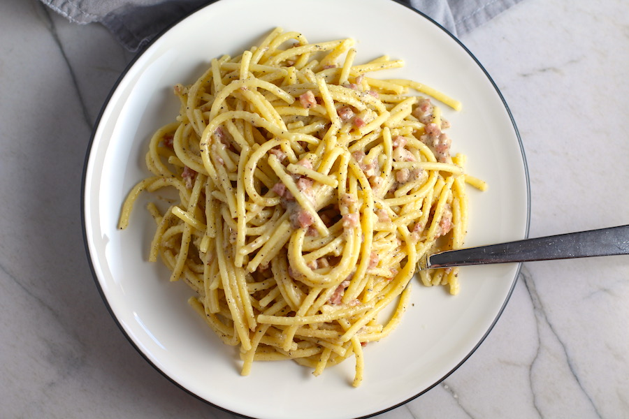Pancetta, Parmesan, and Pepper Pasta on plate with fork. The Pancetta gives a salty and slightly peppery flavor, Parmesan cheese creates a nutty and creamy sauce, and the ground black pepper gives a peppery flavor that makes this pasta stand out. #pasta #easypasta #easydinner #dinner #italian #familydinner #onpotdinners #onepandinners #parmesan