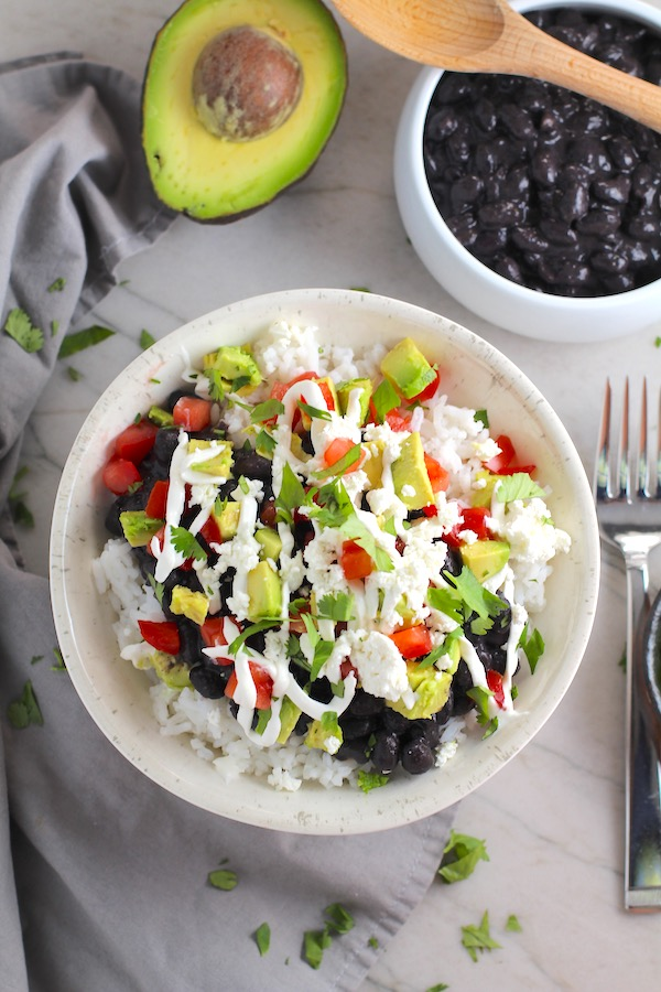 Black Bean Taco Bowl with rice, smoky black beans, avocado, salty Cotija cheese, sour cream, fresh tomato, and bright cilantro. This Black Bean Taco Bowl Bar lets everyone fills their bowl with any of the toppings they want! Perfect for kids. #tacos #tacobowls #healthyfood #dinner #healthydinner #familydinner #kidsdinner #blackbeans #vegetarian