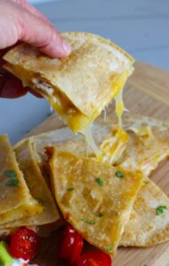 Hand holding Chicken Corn Tortilla Quesadilla triangle with melty cheese pulling. They have crispy edges, a soft gooey center, and are mouthwatering flavor. They have hearty shredded chicken flavored with warm and smoky Mexican spices. Then shredded Pepper Jack cheese and Cheddar is layered to get melty and oozy and delicious. It's an irresistible new easy dinner or appetizer idea. #quesadillas #mexicanfood #enchiladas #familydinner #chicken