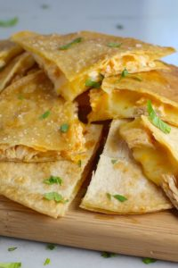 Chicken Corn Tortilla Quesadilla triangles on platter. They have crispy edges, a soft gooey center, and are mouthwatering flavor. They have hearty shredded chicken flavored with warm and smoky Mexican spices. Then shredded Pepper Jack cheese and Cheddar is layered to get melty and oozy and delicious. It's an irresistible new easy dinner or appetizer idea. #quesadillas #mexicanfood #enchiladas #familydinner #chicken