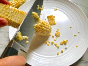 Knife cutting corn kernels off cob for Chilled Golden Corn Soup with Turmeric.  Scallions on top for garnish. It's thick, creamy, silky and delicious.  The entire family will love this easy stovetop corn soup! #summerfood #cornsoup #corn #vegetarian #vegetablerecipes #sides
