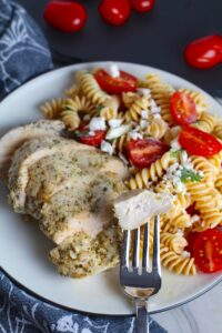Fork with bite of Mediterranean Chicken sliced on plate with a tomato and feta pasta. This Mediterranean Marinade is only a few ingredients, can be made ahead, and is delicious!