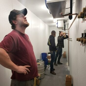 Rio Connelly, left, Proper Brewing Co. brewer and co-owner, inspects the installation of the draft lines at Craft by Proper in early April. Photo Credit: Craft by Proper