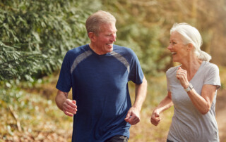 Senior Couple Exercising In Autumn Countryside During Covid 19 Lockdown