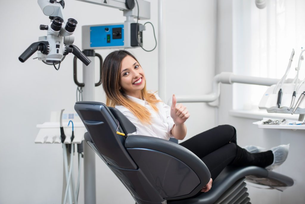 Beautiful female patient with perfect white teeth sitting in dental chair, smiling and showing thumbs up after treatment at modern dental clinic.