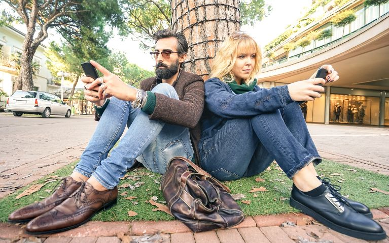 Millennial couple sitting down on the street