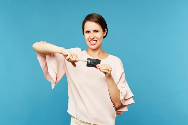 Woman cutting credit card