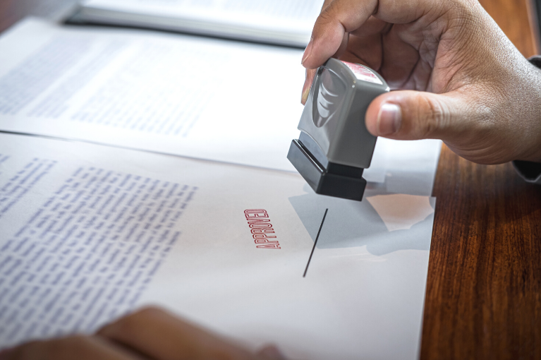 Man stamping contract with Approved