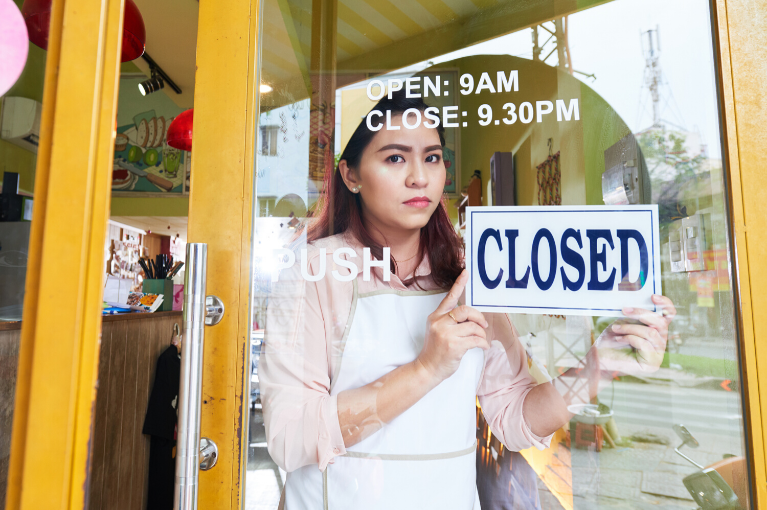 Business owner turning the Closed sign to her bakery