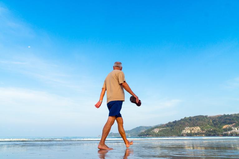Old man walking on the beach