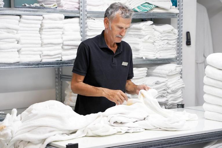 Man folding towels