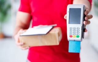 Delivery man holding parcel and POS